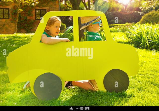 Jungen und Mädchen kniet hinter Karton Freisteller in Form des Auto Stockbild