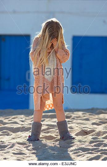 Junge Mädchen stehen am Strand für ihr Gesicht Stockbild