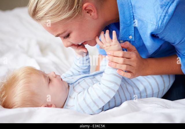 Mutter mit Baby Sohn zu spielen, als sie zusammen im Bett liegen Stockbild