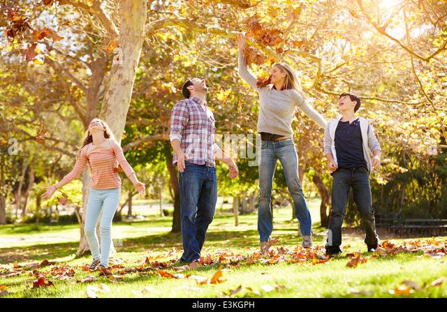 Familie Herbst wirft Blätter In der Luft Stockbild