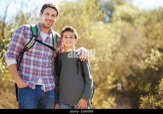 Vater und Sohn wandern im Land tragen Rucksäcke Stockbild