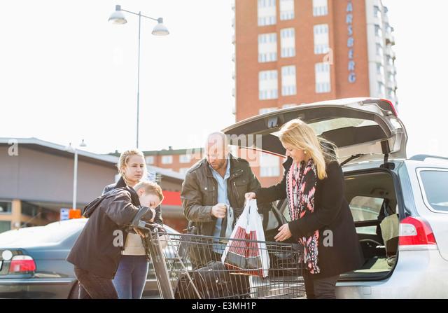 Familie Laden Lebensmittel im Kofferraum eines Autos auf Parkplatz Stockbild