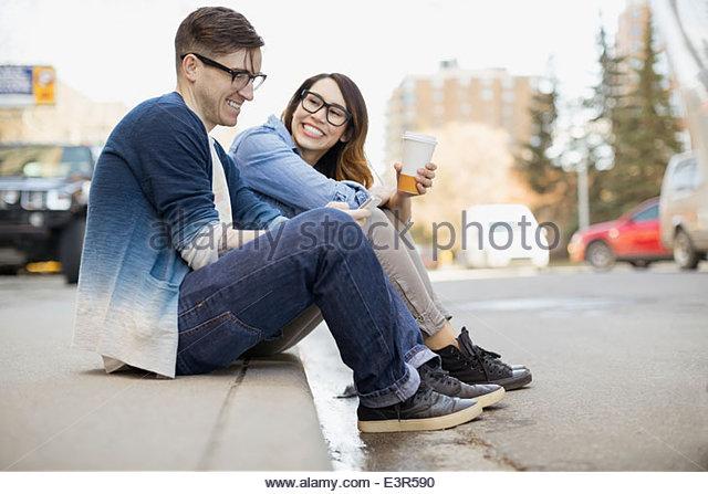 Hipster-paar Kaffeetrinken auf städtischen Bordstein Stockbild