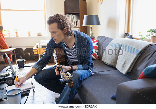 Musiker mit Gitarre Musik im Wohnzimmer zu schreiben Stockbild