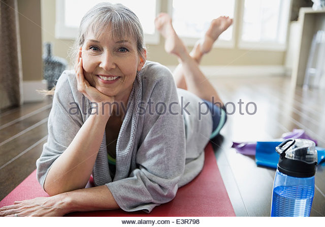 Porträt der lächelnde Frau, die Yoga-Matte auflegen Stockbild