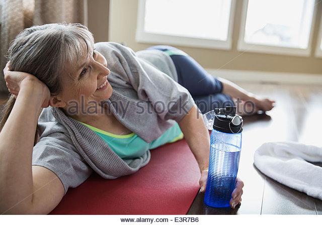 Lächelnde Frau, die Yoga-Matte auflegen Stockbild