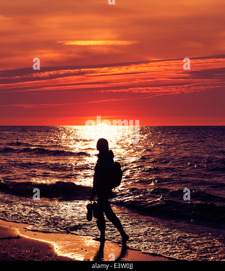 Frau zu Fuß am Strand bei Sonnenuntergang. Stockbild