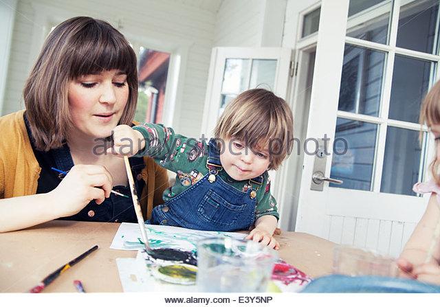 Mutter und zwei Kinder malen im Speisesaal - Stock-Bilder