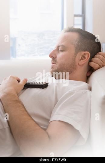 Reifer Mann mit Fernbedienung schlafend auf sofa Stockbild