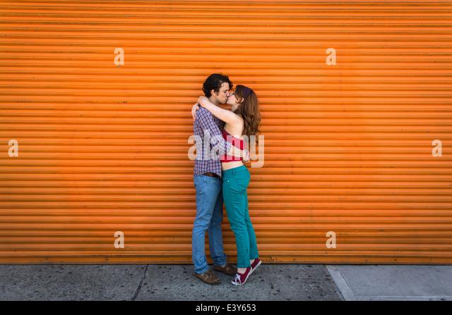 Romantisches Paar küssen vor orange Auslöser Stockbild