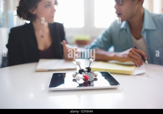 Molekulares Modell des Ethanol-Moleküls, Mann und Frau in der Diskussion im Hintergrund Stockbild
