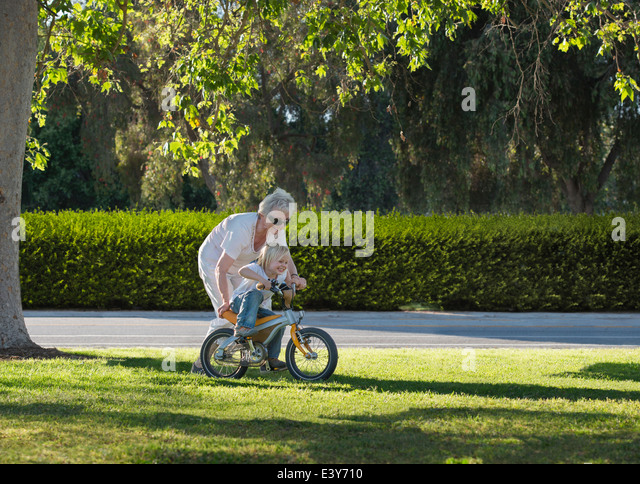Drei Jahre alter Junge mit Großmutter im Park fahren lernen Stockbild