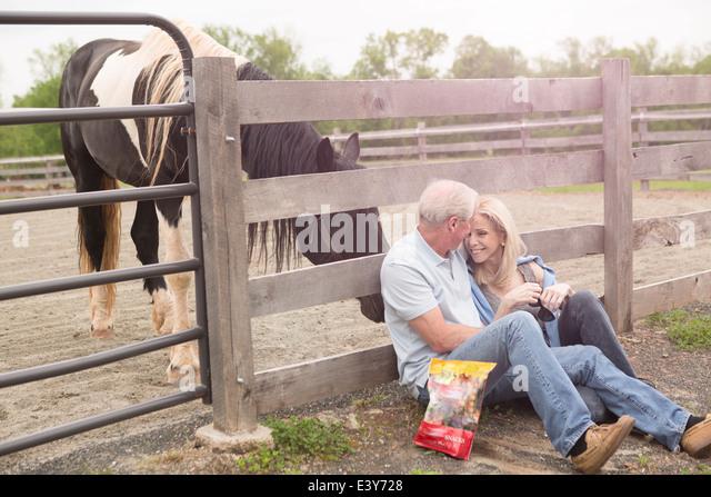 Älteres paar sitzen gegen Zaun und ein neugierig Pferd Stockbild