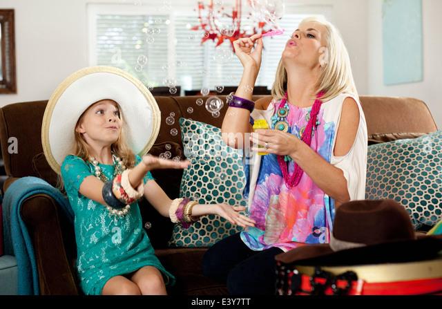 Mutter und Tochter Seifenblasen im Wohnzimmer Stockbild
