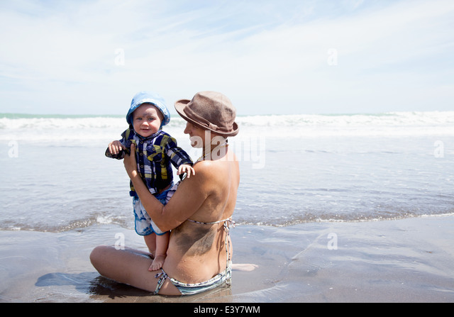 Junge Frau sitzt im Meer mit Baby Sohn Stockbild