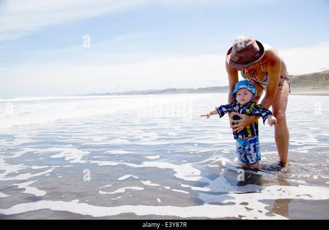 Junge Frau mit Baby Sohn im Meer paddeln Stockbild