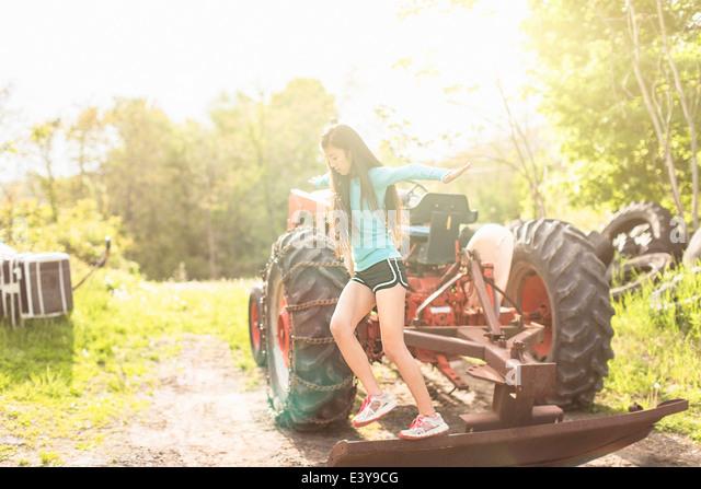 Teenager-Mädchen balancieren auf Traktor Stockbild