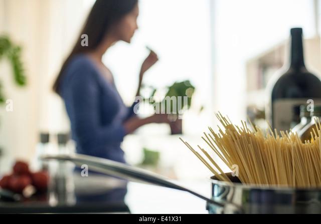 Verschwommenes Bild der jungen Frau, die Zubereitung von Speisen in der Küche Stockbild