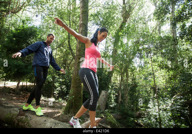 Junge Jogger balancieren auf Baumstamm Stockbild