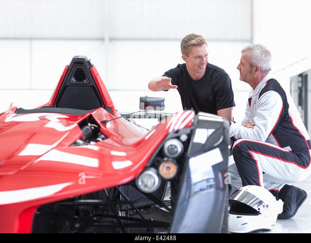 Racing Car Fahrer und Ingenieur mit Supersportwagen Sportwagen Fabrik Stockbild