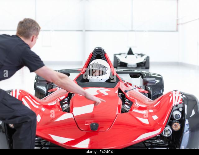 Ingenieur und Rennfahrer in Supersportwagen im Sportwagen-Fabrik Stockbild