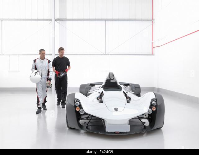 Rennfahrer mit dem Ingenieur und Supersportwagen im Automobilwerk Stockbild
