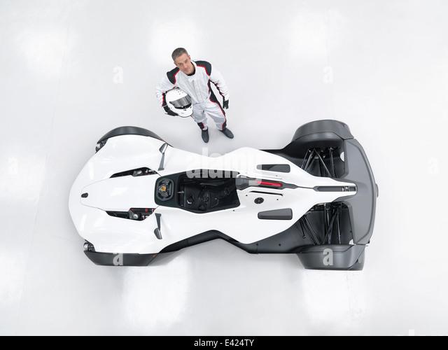 Porträt von Rennfahrer neben Supersportwagen, Draufsicht Stockbild