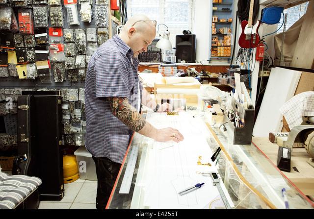 Gitarrenbauer mit Abmessungen bis Blaupause Design auf Tabelle zeichnen Stockbild