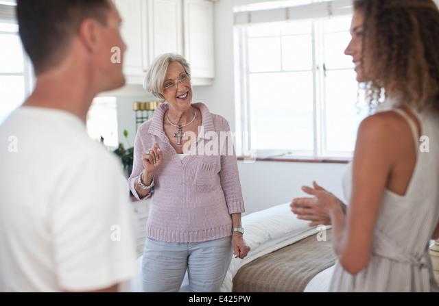 Ältere Frau Führung paar in Ferienwohnung Stockbild