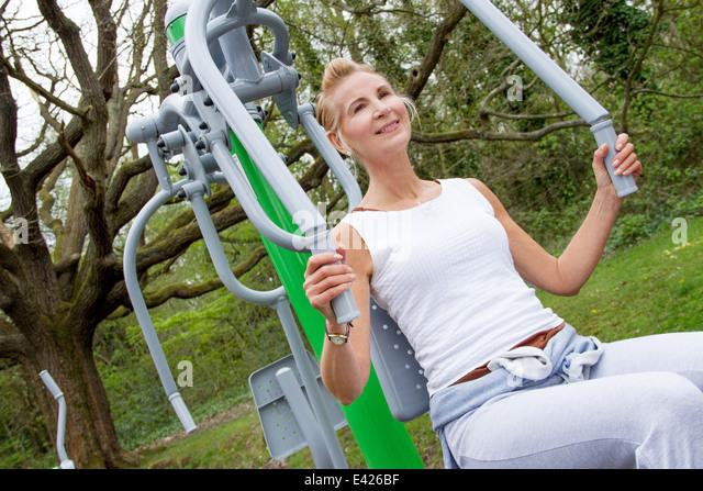 Reife Frau mit Heimtrainer im park Stockbild