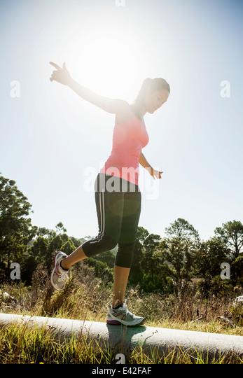 Weibliche Jogger balancieren auf Rohr Stockbild