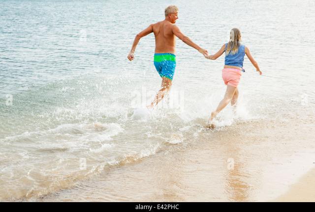 Vater und Tochter laufen und Hand in Hand am Strand Stockbild
