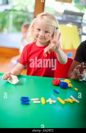 Porträt eines Mädchens zählen mit Fingern im Kindergarten Stockbild