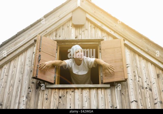 Junge männliche Bäcker stützte sich öffnenden Fenster Rollläden Stockbild