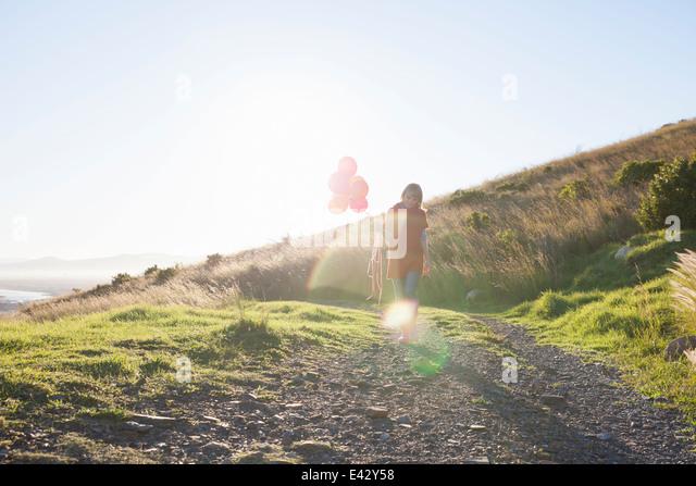 Junge Frau spazieren Feldweg mit Haufen Luftballons Stockbild