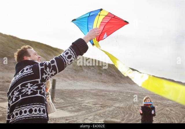 Mitte erwachsener Mann und Sohn bereitet sich Drachen am Strand von Bloemendaal Aan Zee, Niederlande Stockbild