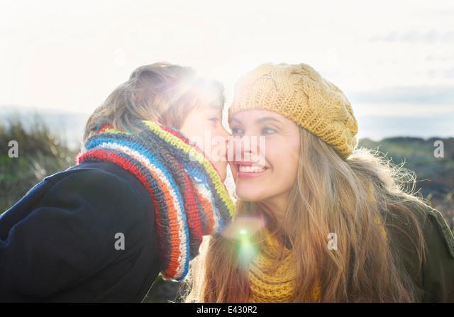 Mitte Erwachsene Frau mit Sohn küsst ihre Wange an Küste Stockbild