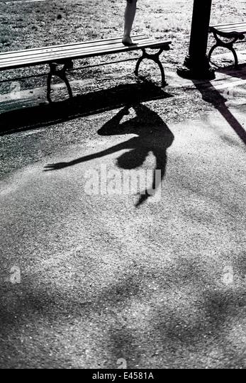 Moderne Tänzerin fällt eine Pose in einem städtischen Park, Schatten Stockbild