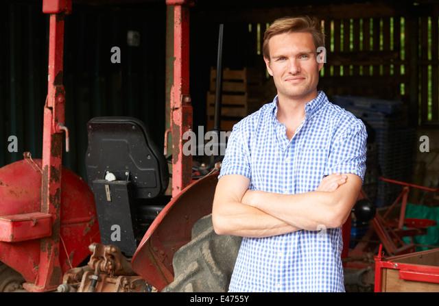 Landwirt stehen neben alten altmodisch Traktor In der Scheune Stockbild