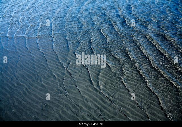 Wellenmuster auf Sandboden und Wellen Stockbild