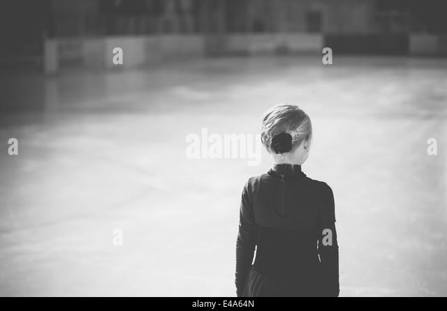Junge weibliche Abbildung Skater stehen auf der Eisbahn beim Wettbewerb, Rückansicht Stockbild