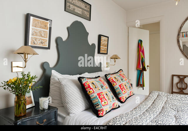 Vintage floral Eiderdaune auf Bett mit Fabindia gestreiften Kissen Fällen und 50er Kissen. Das OKA Kopfteil Stockbild
