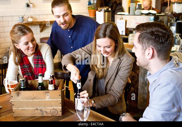 Junge Frau Eröffnung Flasche Bier, Freunde beobachten, Dorset, Bournemouth, England Stockbild