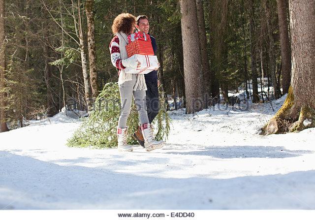 Mann und Frau mit Geschenken und Weihnachtsbaum, im freien Stockbild