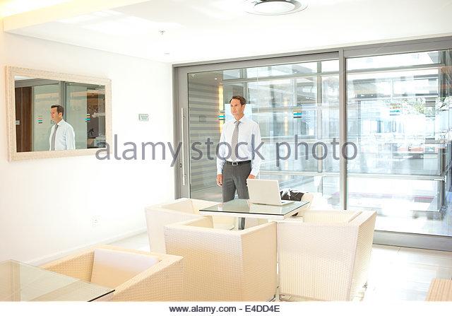 Geschäftsmann, Blick auf sein Spiegelbild im Büro Stockbild