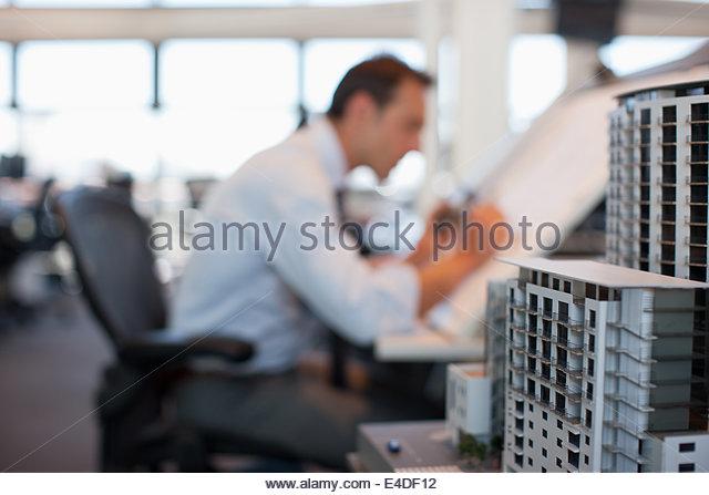 Geschäftsmann am Zeichentisch im Amt zeichnen Stockbild