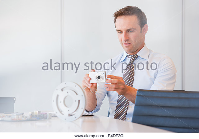 Kaufmann unter Bild des Zahnkranzes mit Digitalkamera Stockbild