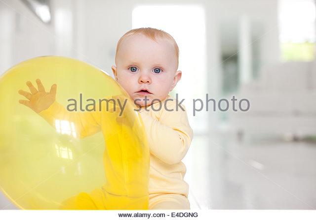 Neugierig Baby mit gelben Ballon Stockbild