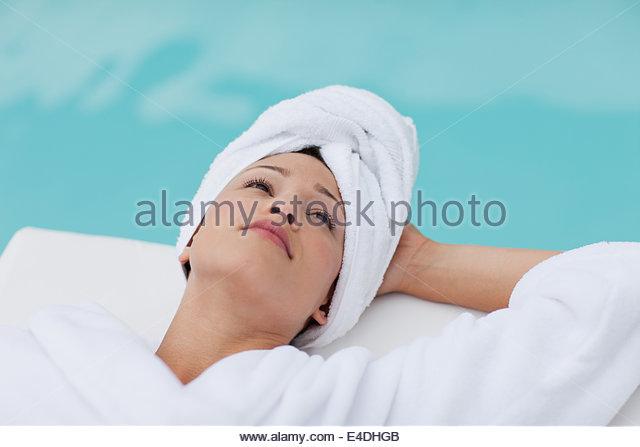 Frau mit Kopf gewickelt Handtuch am Pool legen Stockbild