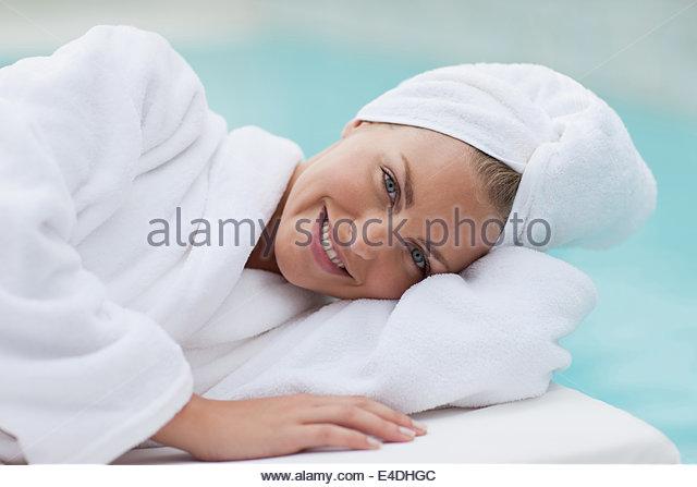 Frau mit Kopf gewickelt Handtuch am Pool zu legen Stockbild